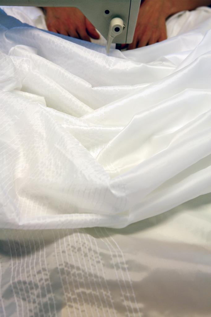 두 손이 흰 천을 미싱 아래로 넣어 미싱기를 돌리고 있다. 흰 천을 일직선으로 뺴고 있는 일자박기를 하는 모습이다