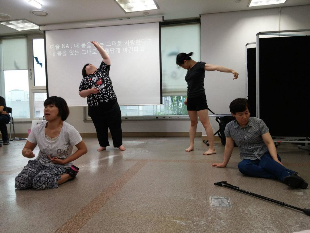 공연을 연습하는 모습이다. 두명의 여성은 앞 쪽에 앉아있으며, 뒷편에는 두 명의 여성이 일어서있다. 뒷쪽 왼편에 있는 여성은 한 쪽 팔을 위로 올리고 한쪽 팔을 굽히고 있으며, 다른 여성은 양 팔을 뒤로 젖히고 있다. 앞쪽의 두 여성은 무릎을 꿇고 연기에 집중하고 있다